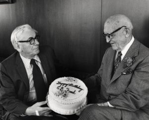 Chancellor Edwin Young presents President Emeritus E. B. Fred with a 90th birthday cake, March 3rd 1977 (S07990)