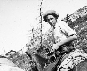 Thomas E. Brittingham, Jr., on horseback in Glacier National Park. The square black object in his hands is probably a camera. 1913. #WI.bls0228