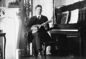 Thomas Brittingham, Jr. sits on a piano bench to play the mandolin. While attending The University of Wisconsin--Madison, Tom was first mandolin in Wisconsin's Mandolin Society. 1914. #WI.bls0057