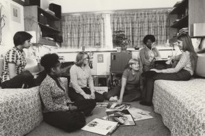 A group of students sit inside a dorm room and listen to records