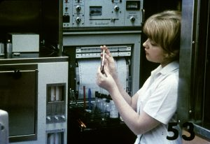 A woman examines a test tube in a lab as a machine behind her prints out readings.