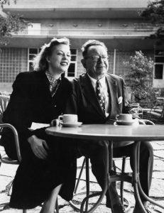 Oskar and Uta Hagen sit outside at a metal table, drinking coffee