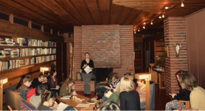 Anna Andrzejewski stands by a fireplace in front of a group of students in a mid-century modern home, lecturing
