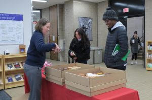 Dean of Students Christina Olstad handing out doughnuts at College Library on Wednesday, November 20