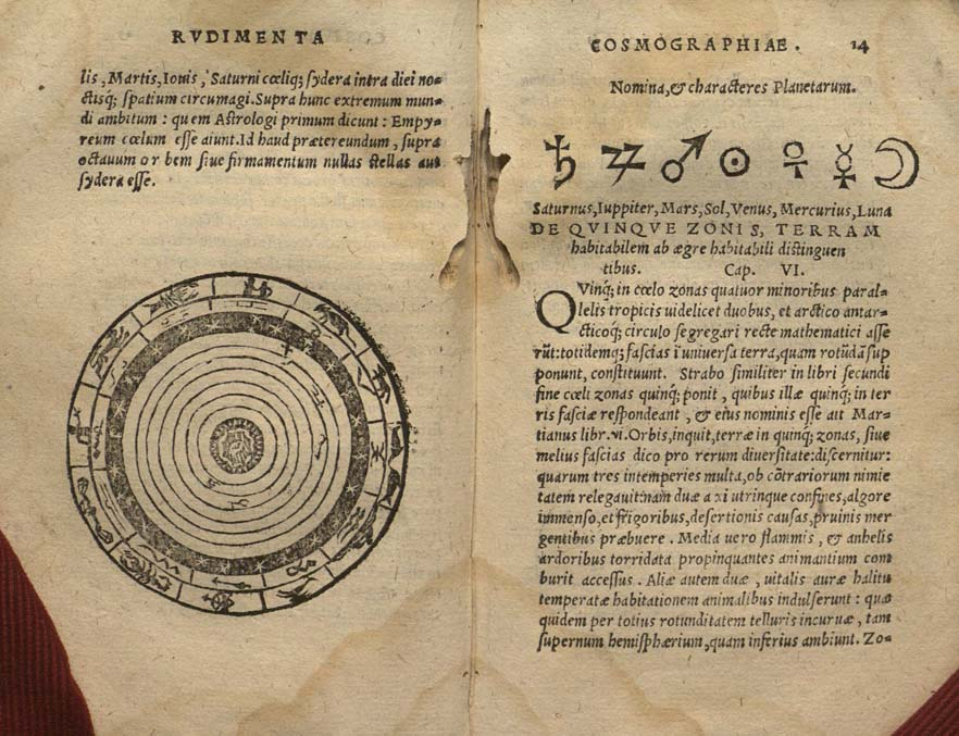 """fol. 13 verso – 14 recto with a woodcut of the celestial spheres, signs of the planets, and evidence of """"bookworm"""" activity"""