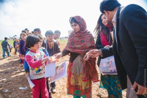 Malala Yousafzai (left), Shiza Shahid (center) and Malala's father, Ziauddin Yousafzai (right), visit with children in Jordan, where the Malala Fund is supporting informal education programs to engage Syrian refugees.  Photo: Tanya Malott/Malala Fund