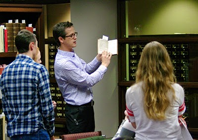 Prof. Joshua Calhoun of the English Department showing a Special Collections book to his students.