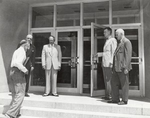 President E.B. Fred, Oscar Rennebohm, Vice President of the Board of Regents, Gilbert Doane, Director of the Library, and Mark Ingraham, Dean of the College of Letters of Science look on as professor Laurance C. Burke carries the first book (the Coverdale Bible from Thordarson Collection) into Memorial Library.