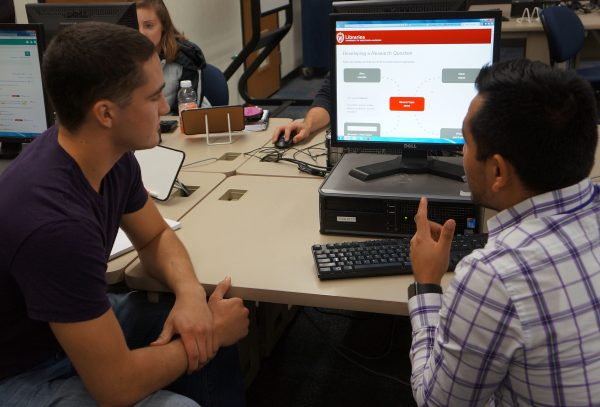 Librarian assisting a student with the Sift & Winnow multimedia online tutorial